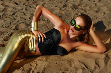 Tanned girl on the sand in sun glass with wet hair and gold jewelry.