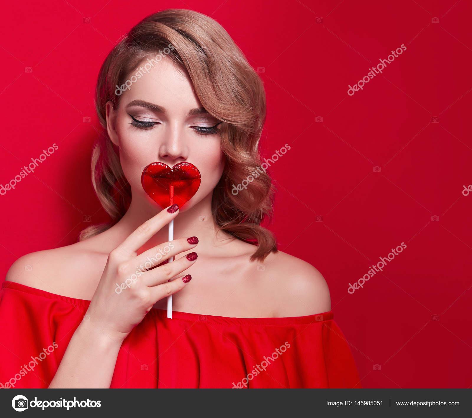 Chica rubia con una piruleta en forma de corazón rojo — Foto de ...
