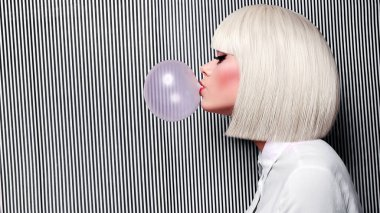Beautiful girl in white wig blew up in pink gum bubble.