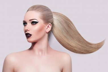 Beautiful young blonde girl with high ponytail. Bright makeup, black arrows, purple lips. Beauty, fashion, health, beauty salon, spa, hairstyle. Smooth skin. Cosmetics.
