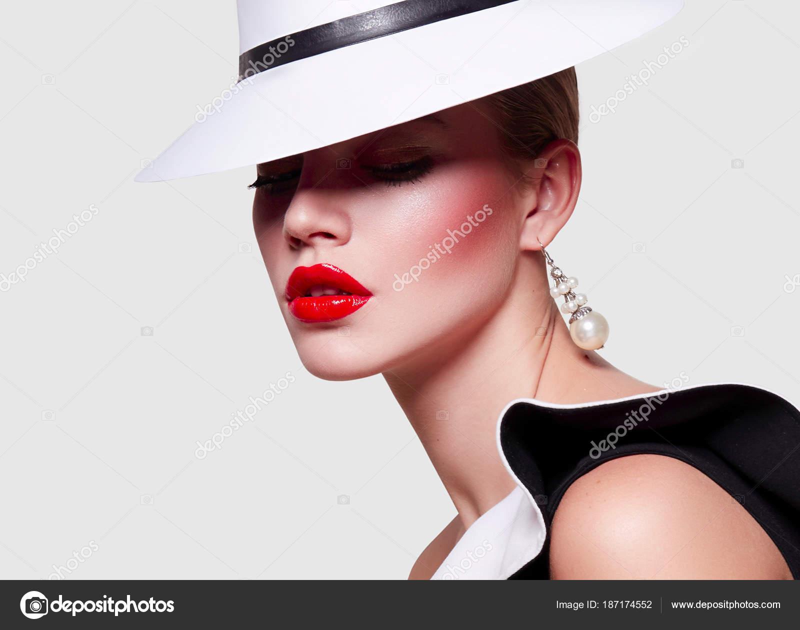 343c53e68615 Bella giovane ragazza elegante in un abito bianco e un abito nero con  valans. Ritratto su priorità bassa bianca. Trucco luminoso - labbra rosse