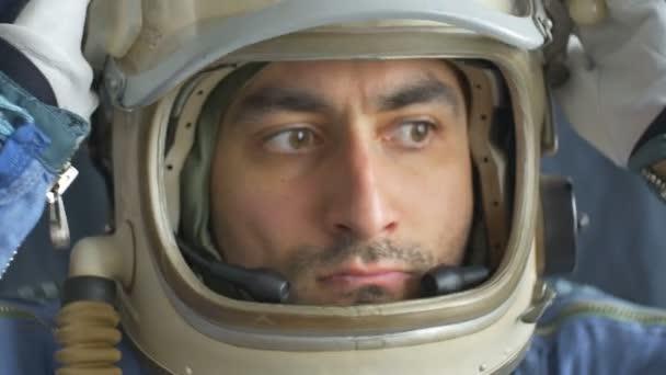 Dunkelhaariger männlicher Astronaut schließt sein Helmfenster.