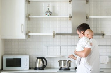 Man in the kitchen holding a child on shoulder, cooking