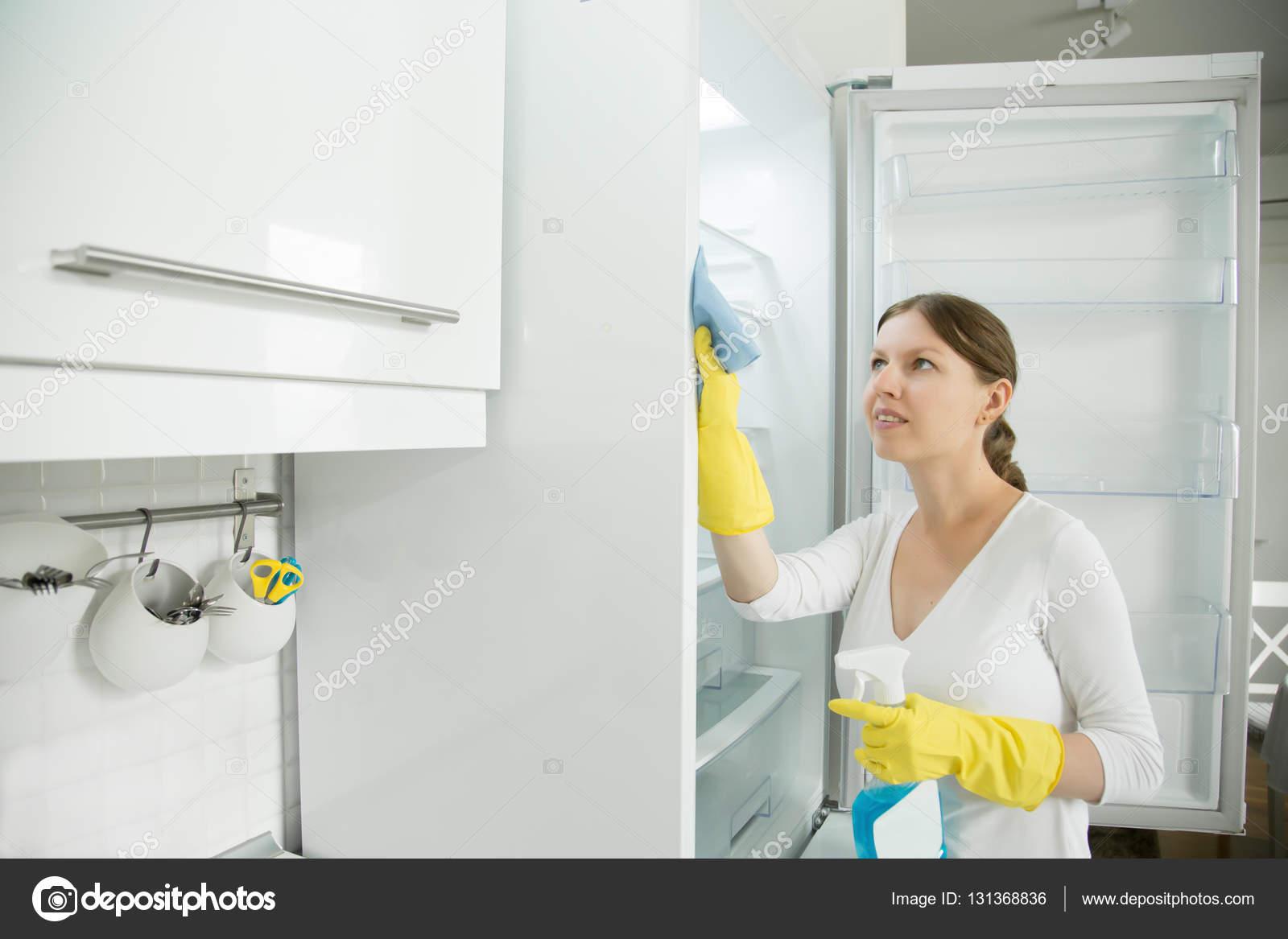 Kühlschrank Reinigen : Junge frau mit gummihandschuhen den kühlschrank reinigen