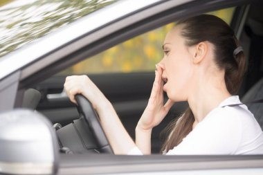 Young woman holding her head at steering wheel