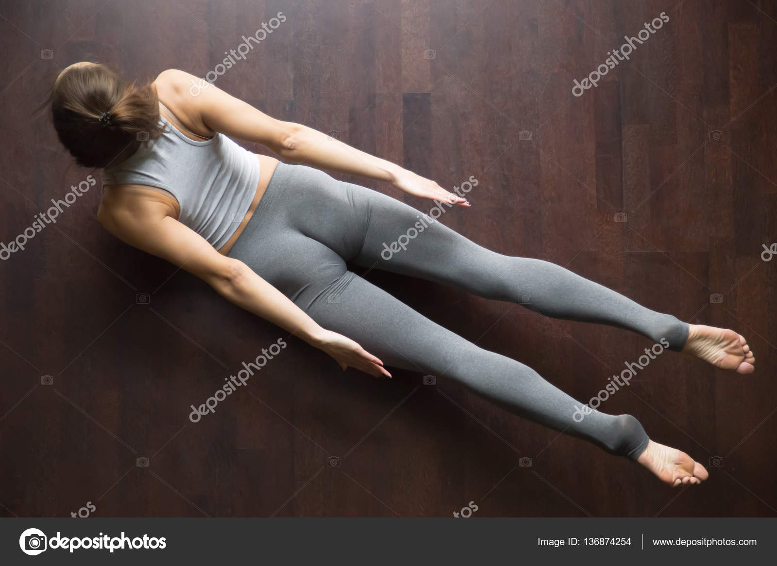 Beautiful Young Model Working Out In Home Interior Doing Yoga Or Pilates Exercise On Wooden Floor Double Leg Kicks Salabhasana Locust Pose Top View