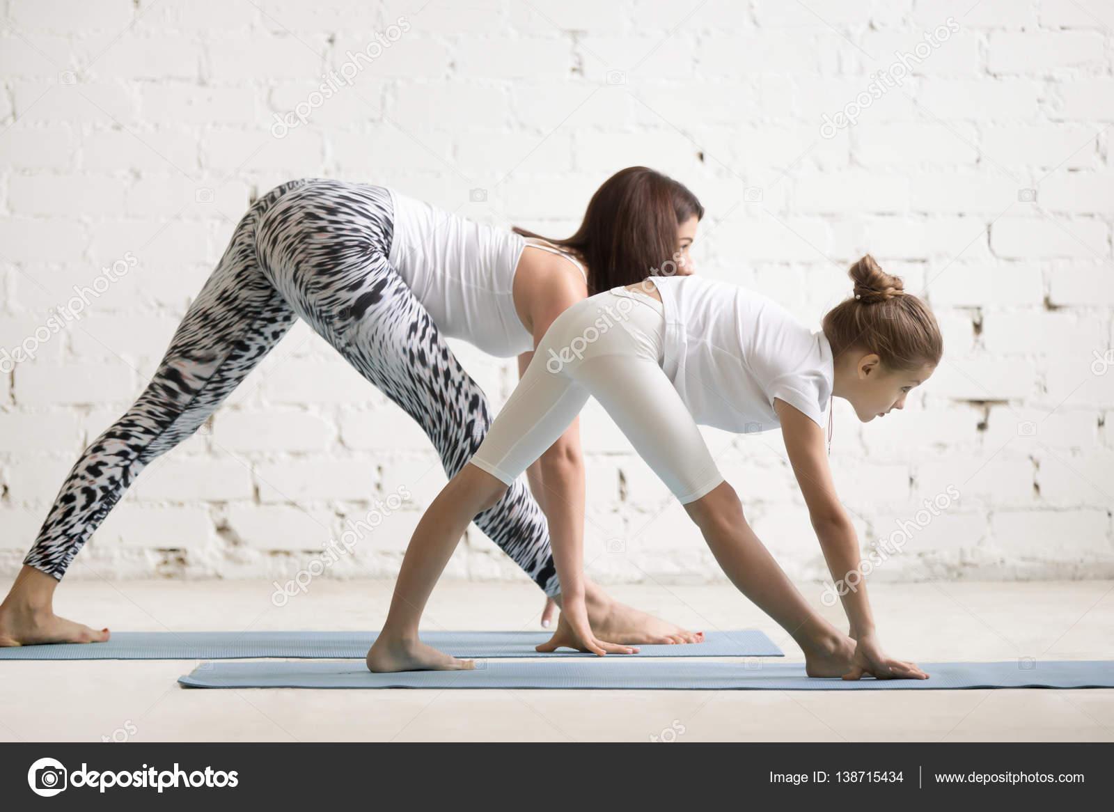 bf1afd52813f Bambini femminile insegnante di yoga, una bambina di formazione, pratica  dello yoga, in piedi in esercizio One Sided piegare, Parsvottanasana posa,  ...