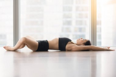 Young attractive woman in Reclined Butterfly pose against floor