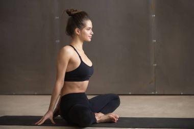 Young attractive woman in baddha konasana pose, grey studio back