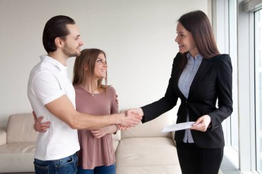Smiling couple shaking hands with estate agent on meeting indoor