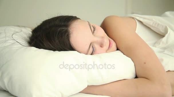 Mladá šťastná žena spí v posteli