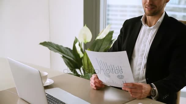 Handsome male boss studying statistic report, satisfied with company growth