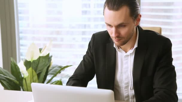 Attractive businessman working on laptop in office, looking at camera
