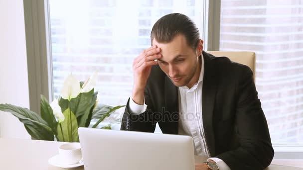 Unavení, přepracovaní mladý podnikatel, zíval a kontrola času na pracovišti