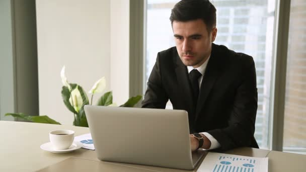 Confident young businessman using laptop at office, looking at camera