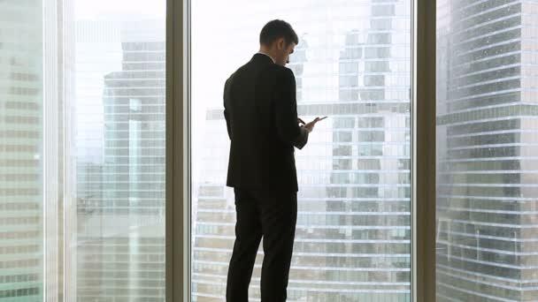 Pohled zezadu na podnikatel stojící poblíž celovečerní okna pomocí tabletu