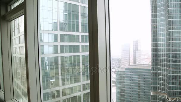 Úspěšný mladý podnikatel přichází do podlahy a stropu okna, při pohledu na panorama