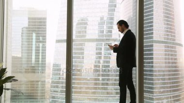 Confident young businessman standing near big window using tablet smartphone