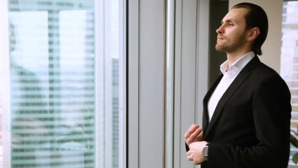 Successful self-satisfied businessman standing at office window, smiling, looking outside