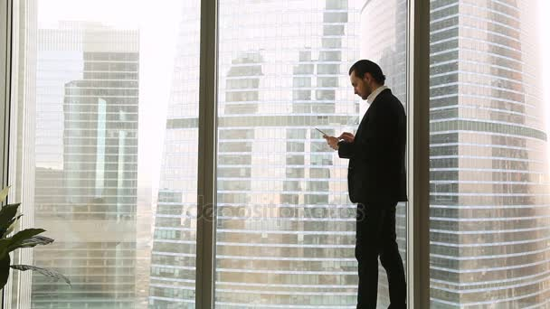 Magabiztos fiatal üzletember közelében nagy ablak használ a táblaszámítógép smartphone