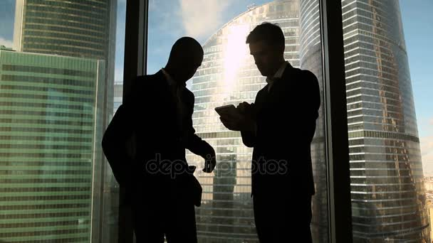 Multicultural business partners handshaking on meeting against full length window