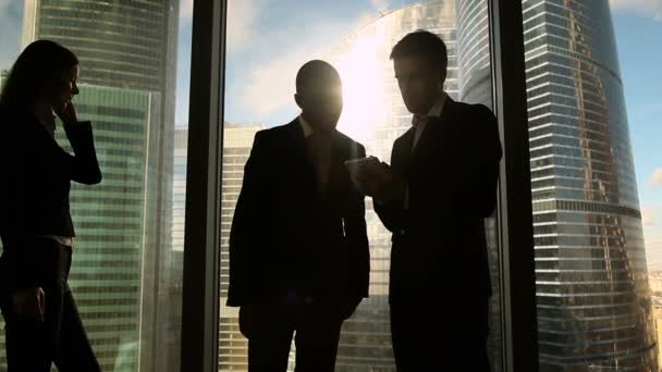 Two multicultural businessmen talking and handshaking, standing by office window