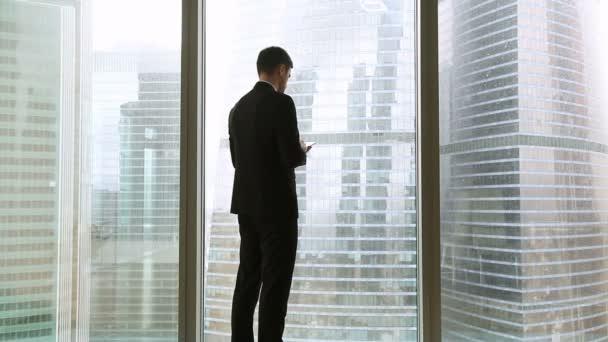 Veselá podnikatel a podnikatelka setkání doma proti plnohodnotné okno, třes rukou, žena dává dokumenty na mužský kolega v kanceláři s městské mrakodrapy v pozadí