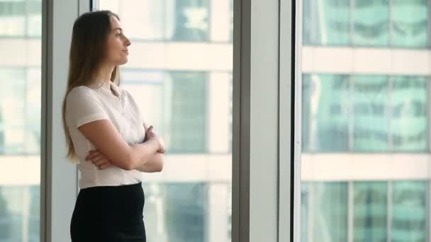 Happy usměvavá podnikatelka uvažuje o panoráma na pozici okna velké kanceláře