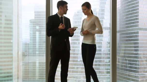 Businessman and businesswoman talking handshaking on meeting against full-length window