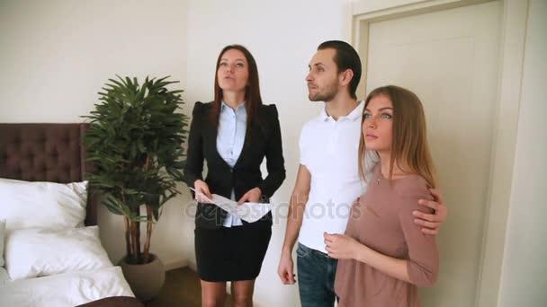 Női ingatlanügynök értekezlet-fiatal pár, bemutatva a apartman hálószoba