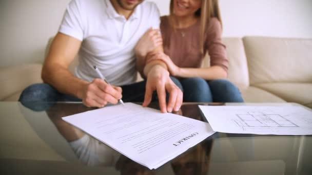 Glückliches junges Paar unterzeichnen Vertrag und umarmt, Hypothek Investitionen