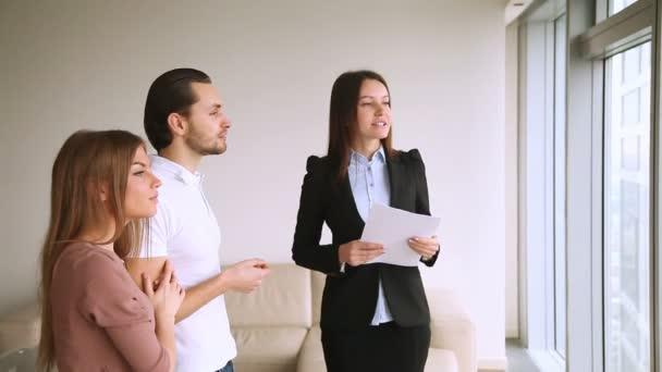 Realitní agent ukazující plochý a infrastruktura v okolí klientům