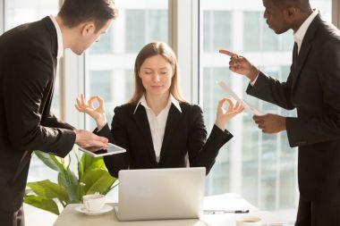 Beautiful businesswoman meditating at workplace, ignoring work a