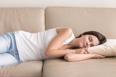 Pretty woman takes short nap during day on sofa