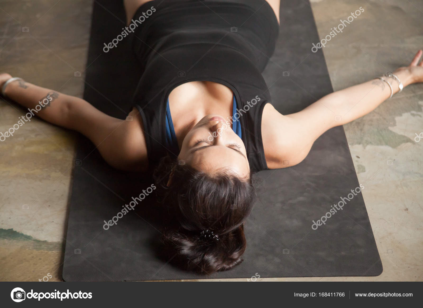 young attractive woman in corpse pose studio floor background