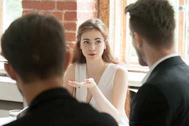 Young female employee sharing opinion with colleagues at work.