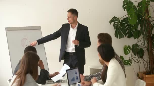 Successful caucasian businessman giving presentation in boardroom for multi-ethnic team