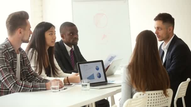 Multi-ethnic business team sharing ideas sitting at conference office table