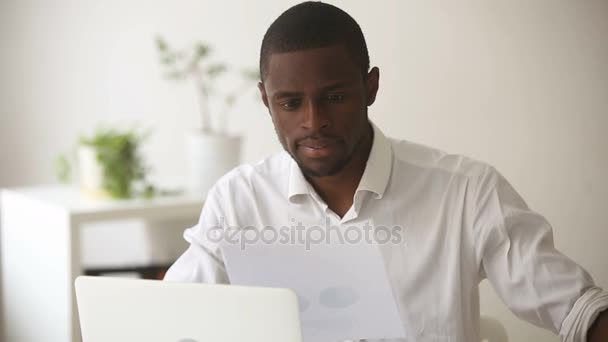 African american businessman analyzing financial stats infographic information at workplace