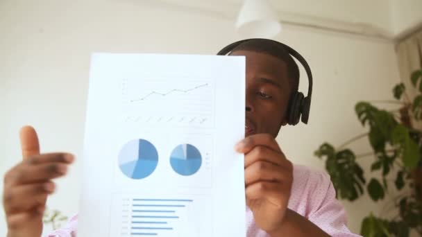 African businessman talking by videocall, showing document stats at webcam