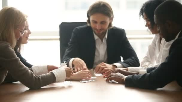 Multi-ethnic business group assembling jigsaw puzzle together at conference table