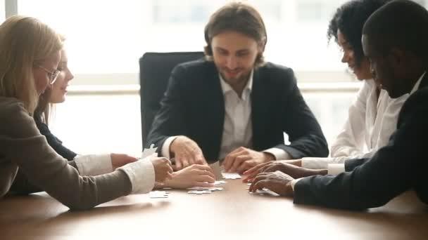 Multietnické obchodní skupina montáže jigsaw puzzle společně na konferenční stůl