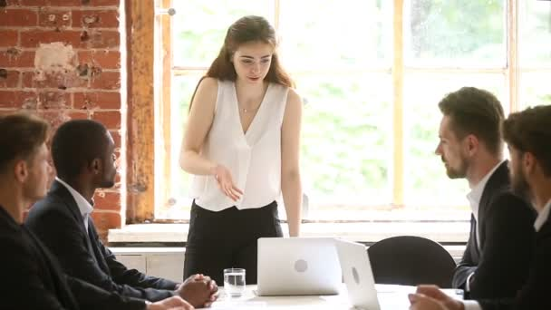Strict woman boss reprimanding male employees, showing authority at meeting