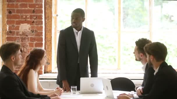African american boss discussing project at meeting with diverse team