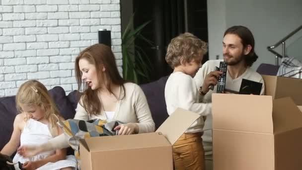 Šťastná rodina s dětmi vybalování krabic na gauči v obývacím pokoji