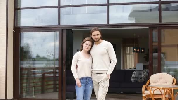 Usmívající se pár při pohledu na fotoaparát objímání stojící na terase domu