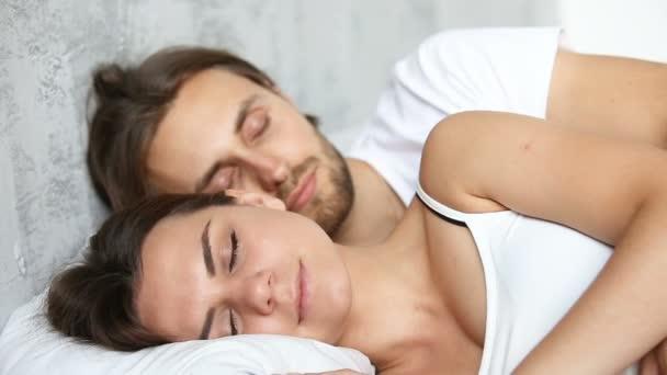 Mladý pár, spí v posteli, ležící srostlými na bílém prádle