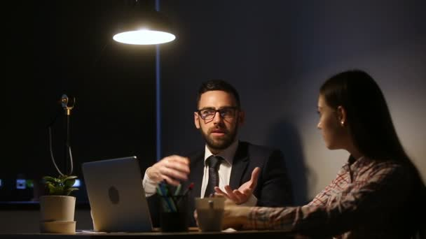 Serious manager teaching instructing intern late in office with computer