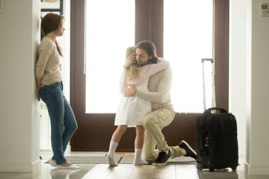 Sad father hugging little daughter before leaving for long trip