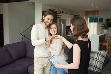 Happy young couple renters getting keys of new rental home